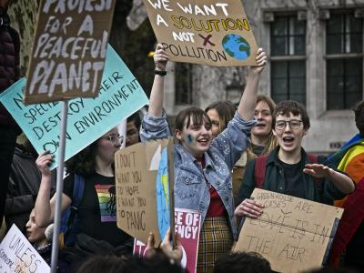 school children holding placards at climate rally